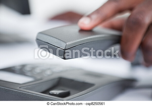 Close up of a masculine hand holding a phone handset - csp8250561