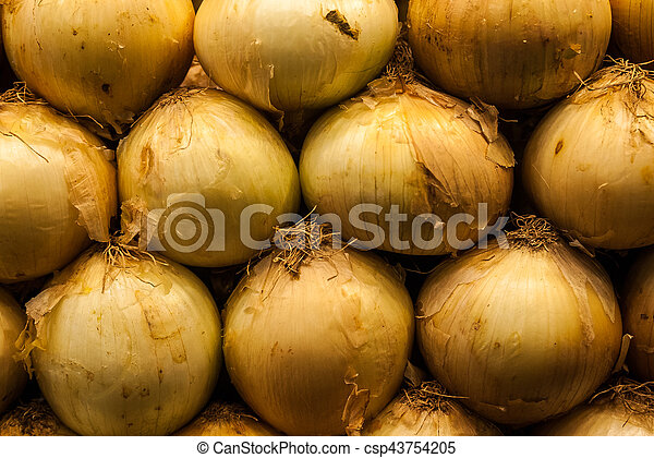 Close up of a pile of yellow onions on the market - csp43754205