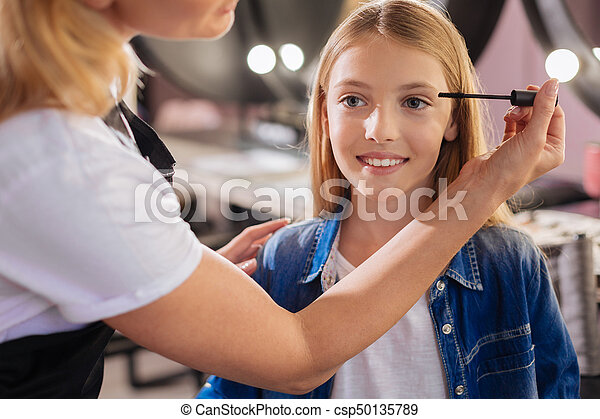Close up of a pretty girl having mascara applied - csp50135789