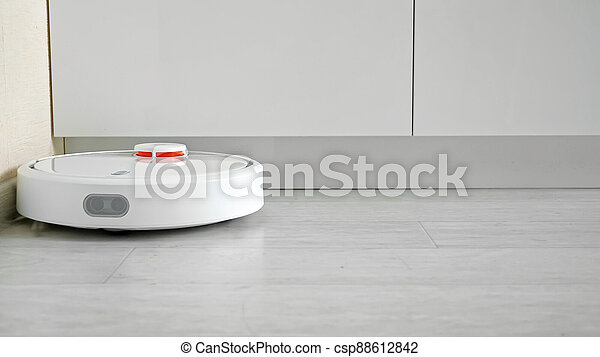 Close-up of a robot vacuum cleaner driving on the floor - csp88612842