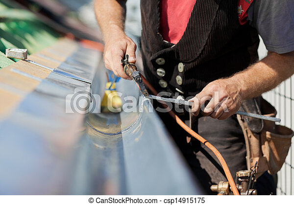 Close-up of a roofer applying weld into the gutter - csp14915175