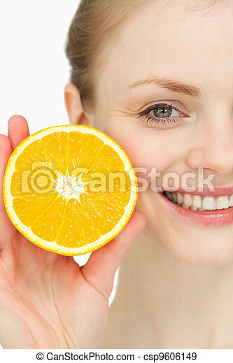 Close up of a smiling woman holding an orange - csp9606149
