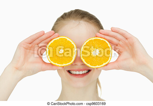Close up of a smiling woman placing oranges on her eyes - csp9603169