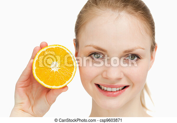 Close up of a smiling woman presenting an orange - csp9603871