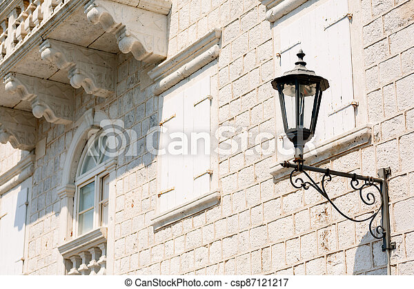 Close-up of a street lamp on the wall of a house under a balcony on a sunny day. - csp87121217