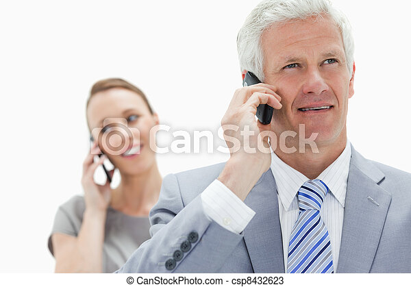 Close-up of a white hair businessman talking on the phone with a smiling woman in background - csp8432623