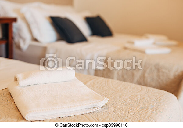 Close-up of a white towel on the made bed against the backdrop of a bed with white and black pillows. - csp83996116