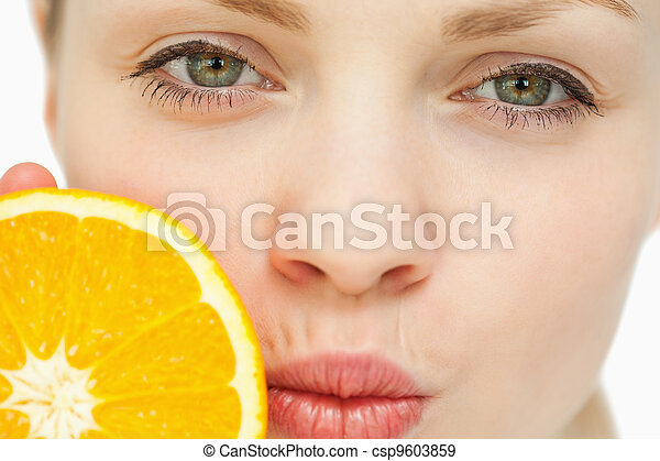 Close up of a woman placing an orange near her mouth - csp9603859