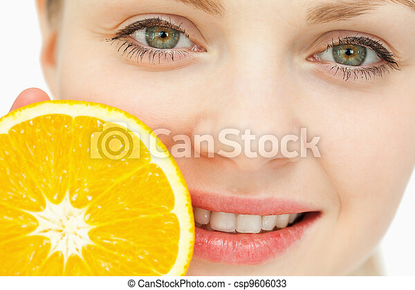 Close up of a woman placing an orange near her lips - csp9606033