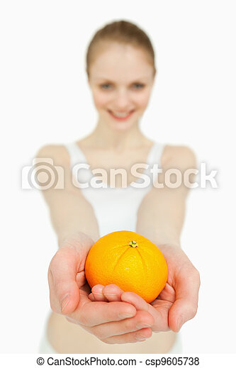 Close up of a woman presenting a tangerine - csp9605738