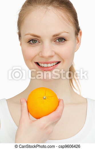 Close up of a woman presenting an orange while smiling - csp9606426