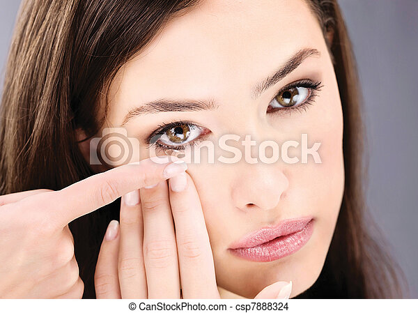 Close up of a woman putting contact lens in her eye - csp7888324