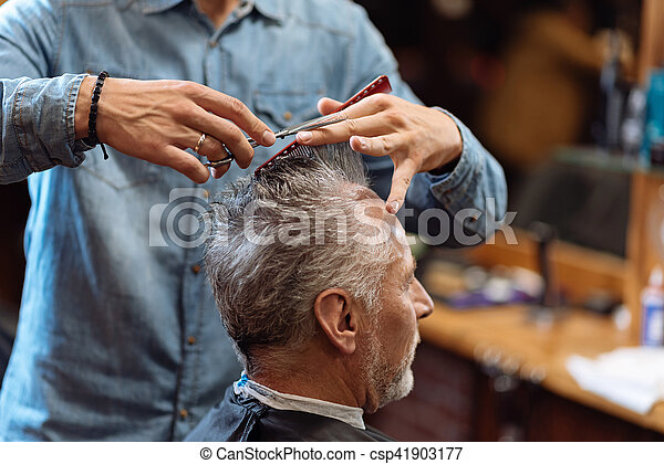Close up of barber during haircut for grey-haired man - csp41903177