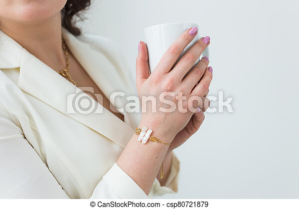 Close up of beautiful female hands holding big white cup of cappuccino coffee. - csp80721879