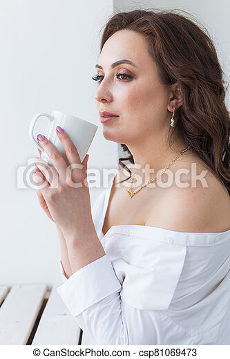 Close up of beautiful female hands holding big white cup of cappuccino coffee. - csp81069473