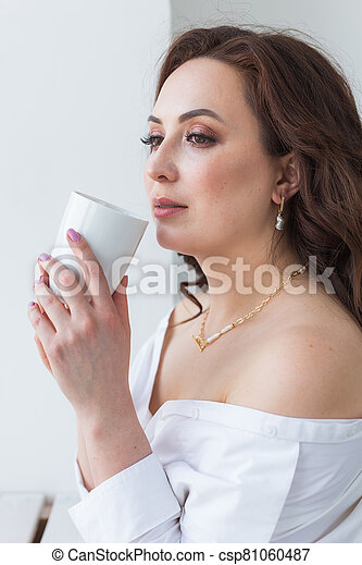 Close up of beautiful female hands holding big white cup of cappuccino coffee. - csp81060487