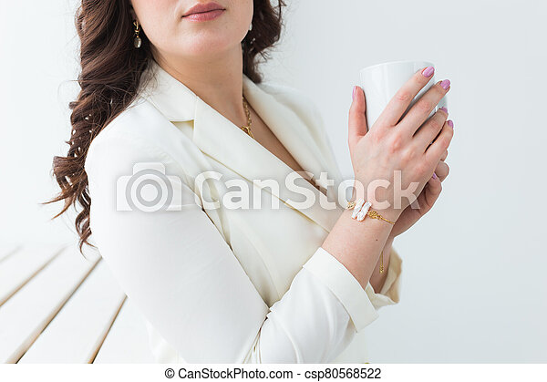 Close up of beautiful female hands holding big white cup of cappuccino coffee. - csp80568522