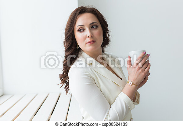 Close up of beautiful female hands holding big white cup of cappuccino coffee. - csp80524133