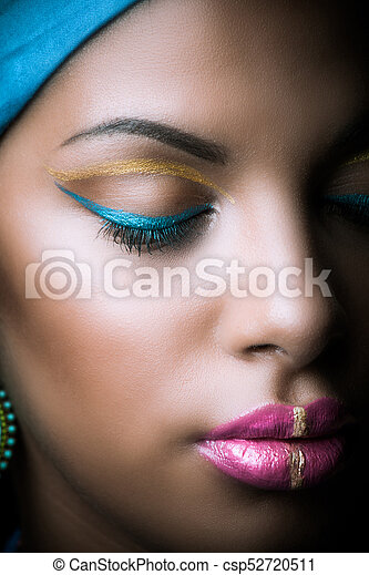 close up of black African woman face with golden and blue makeup - csp52720511