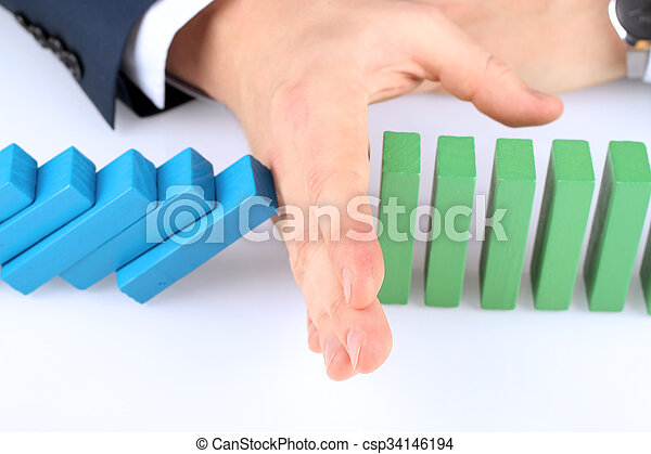 Close-up Of Businessman Stopping The Effect Of Domino With Hand At Desk - csp34146194