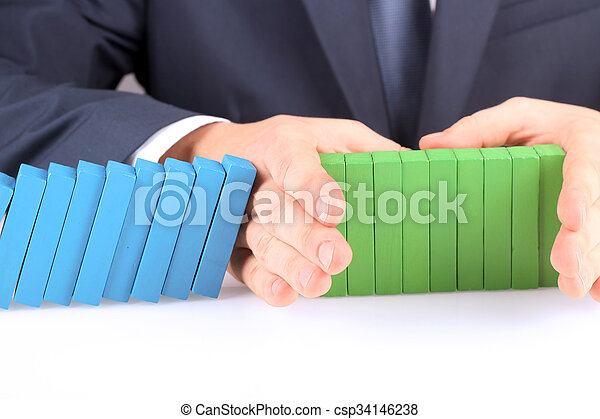 Close-up Of Businessman Stopping The Effect Of Domino With Hand At Desk - csp34146238