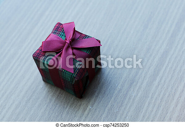 Close up of christmas gift box with old wooden table backgrounds - csp74253250