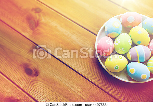 close up of colored easter eggs on plate - csp44497883
