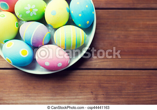 close up of colored easter eggs on plate - csp44441163
