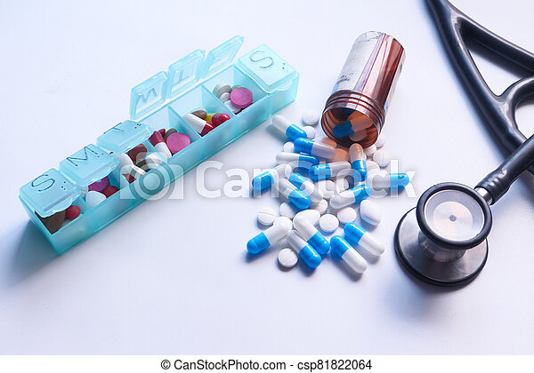 Close up of colorful capsule , pill box and stethoscope on white background - csp81822064