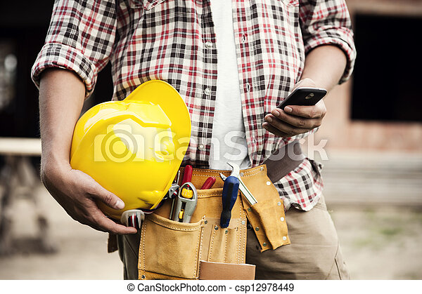 Close-up of construction worker texting on mobile phone - csp12978449