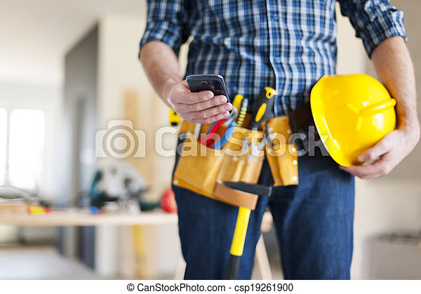 Close up of construction worker with mobile phone - csp19261900