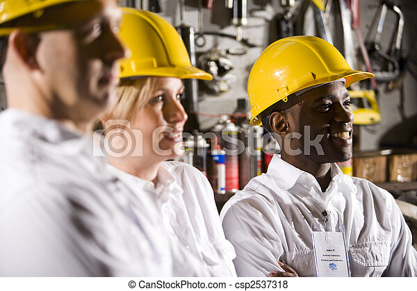 Close up of coworkers wearing hard hats - csp2537318