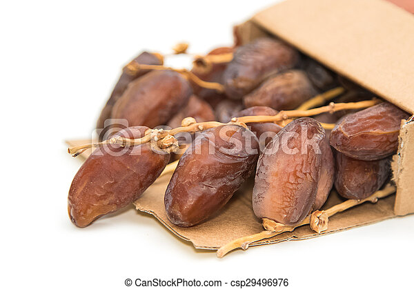 close up of dried dates in paper box on white background - csp29496976