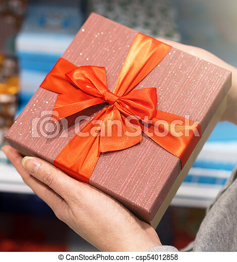 Close-up of female hands holding gift box. - csp54012858