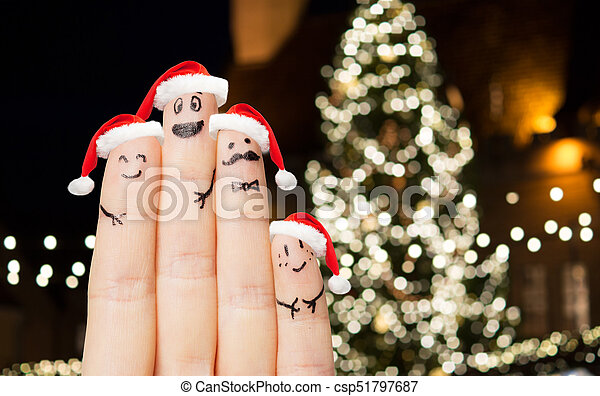 Close up of fingers in santa hats at christmas. Holidays, family and ...