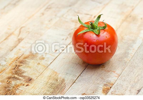 Close-up of fresh, ripe tomatoes on wood background. - csp33525274