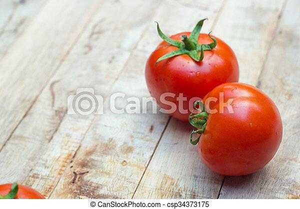 Close-up of fresh, ripe tomatoes on wood background. - csp34373175