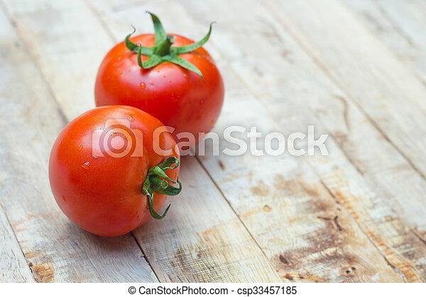 Close-up of fresh, ripe tomatoes on wood background. - csp33457185