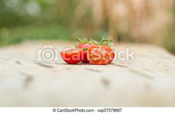 Close-up of fresh, ripe tomatoes on wood background. - csp37079667