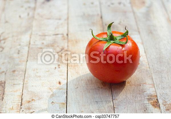 Close-up of fresh, ripe tomatoes on wood background. - csp33747757