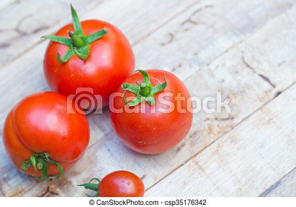Close-up of fresh, ripe tomatoes on wood background. - csp35176342