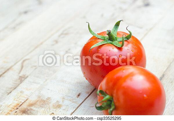 Close-up of fresh, ripe tomatoes on wood background. - csp33525295