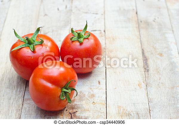 Close-up of fresh, ripe tomatoes on wood background. - csp34440906