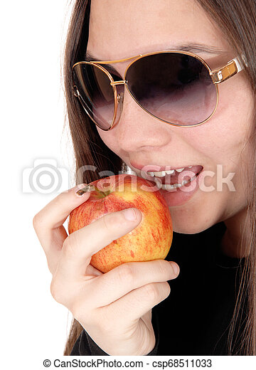 Close up of girl eating a red apple with sunglasses - csp68511033