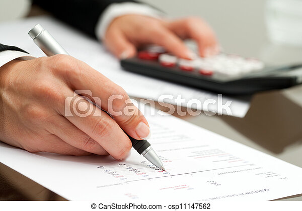 Close up of hand with pen on accounting document. - csp11147562