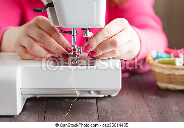 Close-up of hands working on a sewing machine - csp35014435