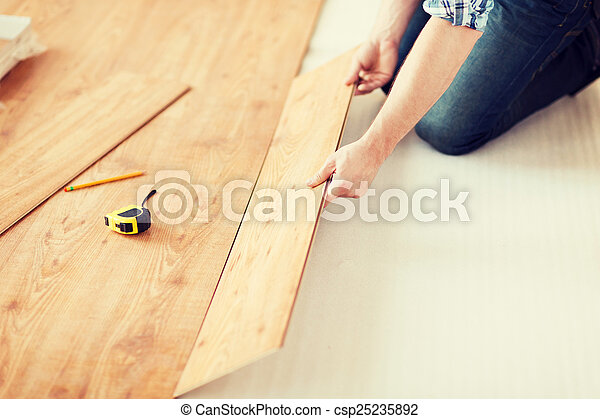 close up of male hands intalling wood flooring - csp25235892