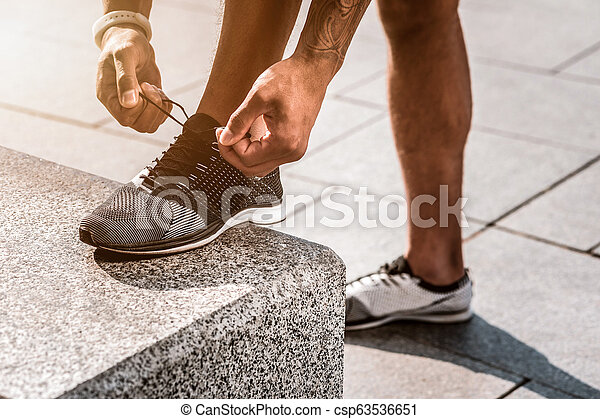 Close up of male hands lacing the shoes - csp63536651