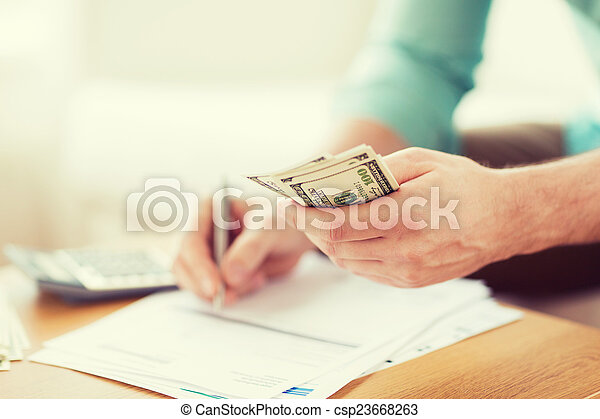 close up of man counting money and making notes - csp23668263