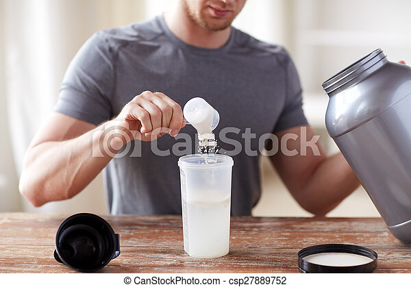 close up of man with protein shake bottle and jar - csp27889752